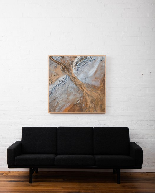 Framed aerial photo in browns and grey in timber frame above sofa