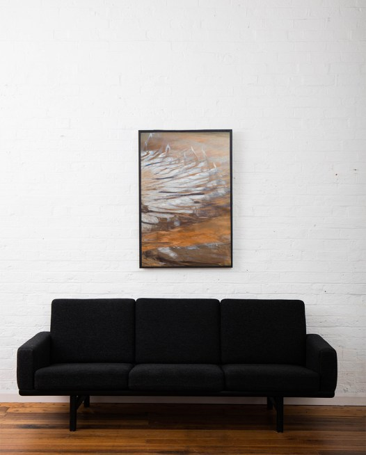 An aerial landscape photo of Australia in brown yellow and silvery colour framed in black timber above sofa