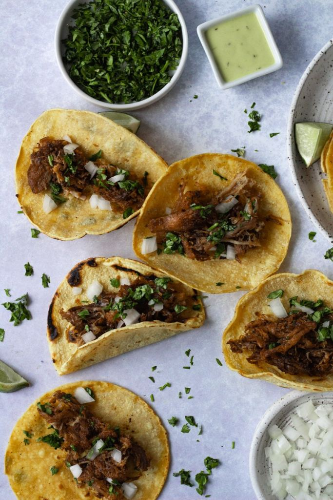 crispy carnitas on tacos with cilantro and onions