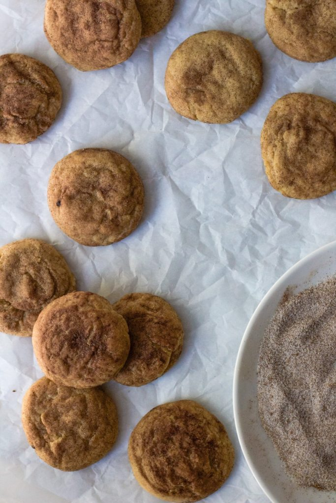 chai snickerdoodle cookies on parchment paper with plate of chai sugar mix in corner