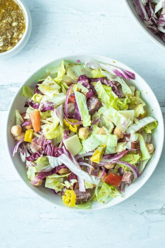 italian chopped salad mixed together in bowl with dressing