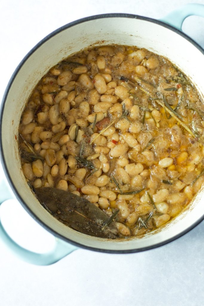rosemary bacon beans in pot before crispy bacon is put on top