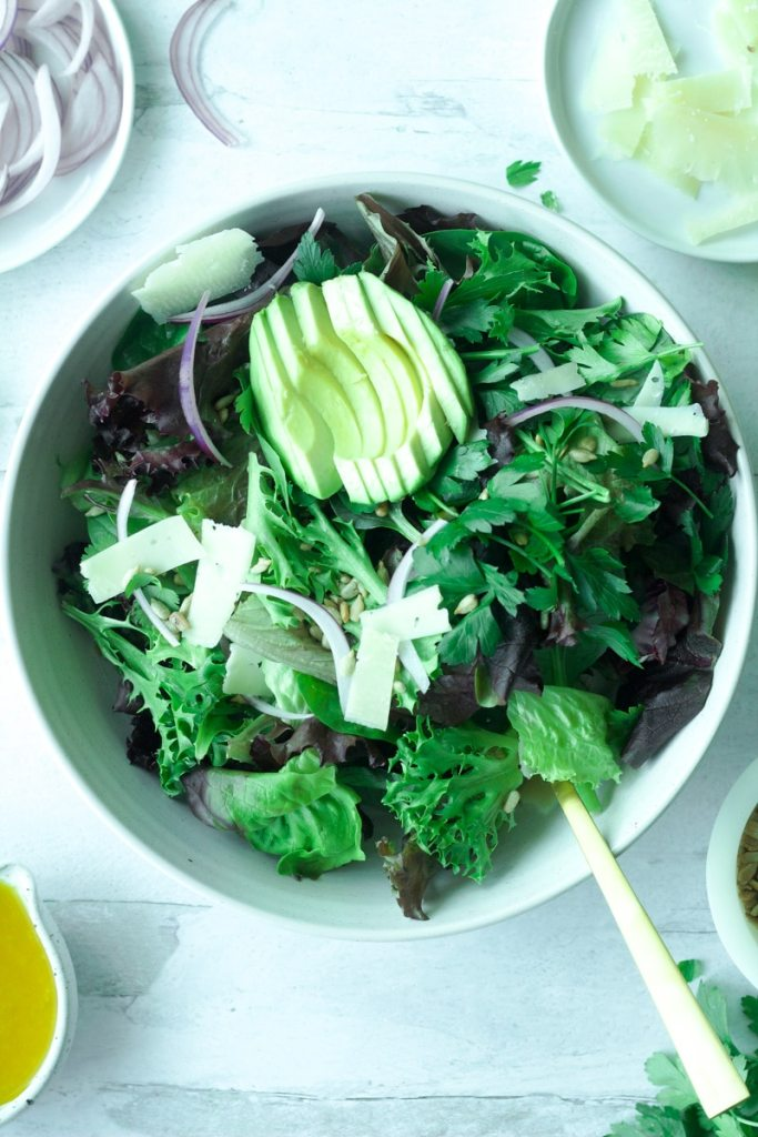Big bowl of salad greens topped with sliced avocado and shaved parmesan cheese with gold fork on side