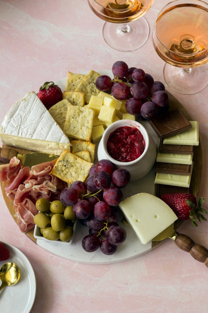 cheese board with cheese, fruits, snacks and two glasses of rose wine
