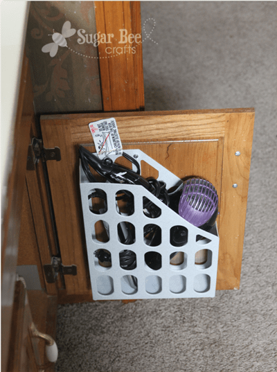 Install a magazine holder inside of your bathroom cabinet to store your hair dryers, flat irons, etc.