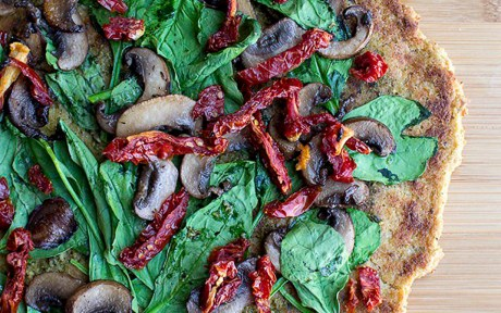 Vegan Gluten-Free Cauliflower Crust Pizza topped with spinach mushrooms and sun-dried tomatoes 1