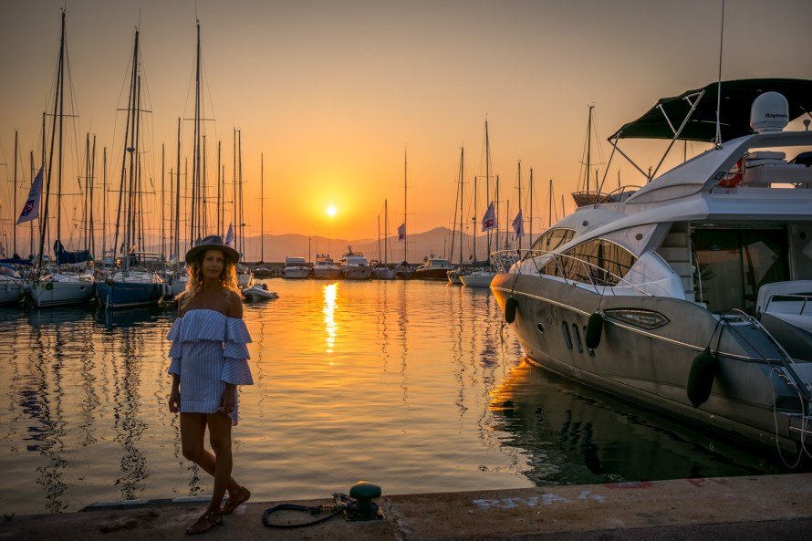 girl in dress in a harbour with sailboats at sunet