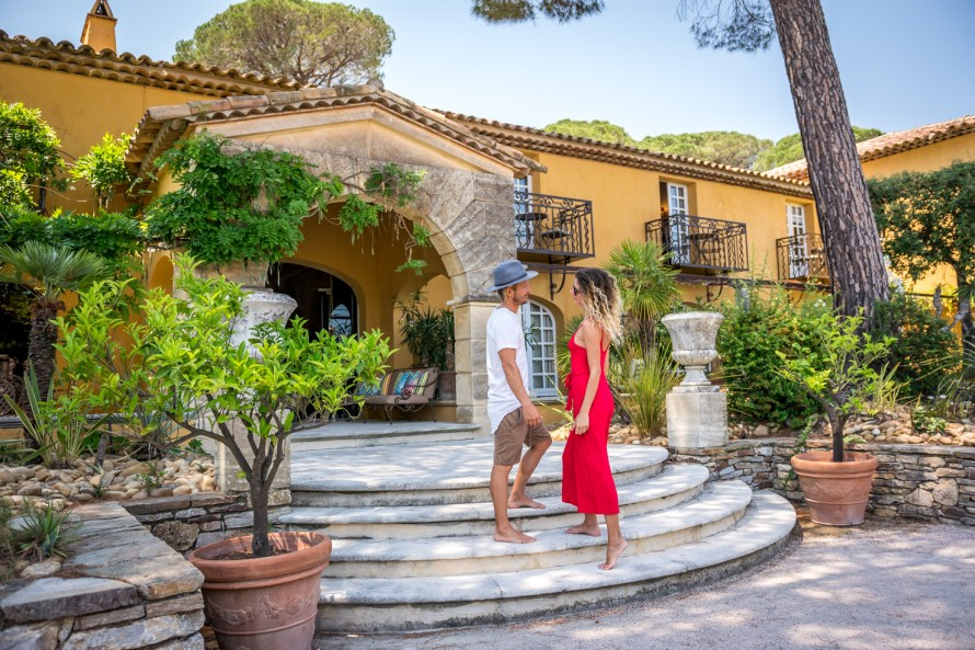 Travel couple standing on stairs of the entrance to Villa Marie Saint Tropez