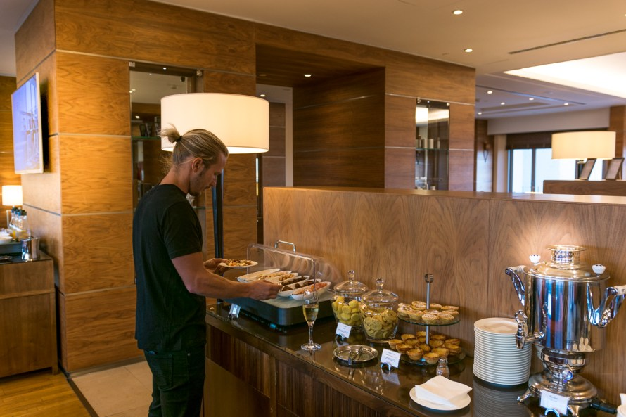 man with ponytail snacking at an Executive lounge at Corinthia Hotel Lisbon