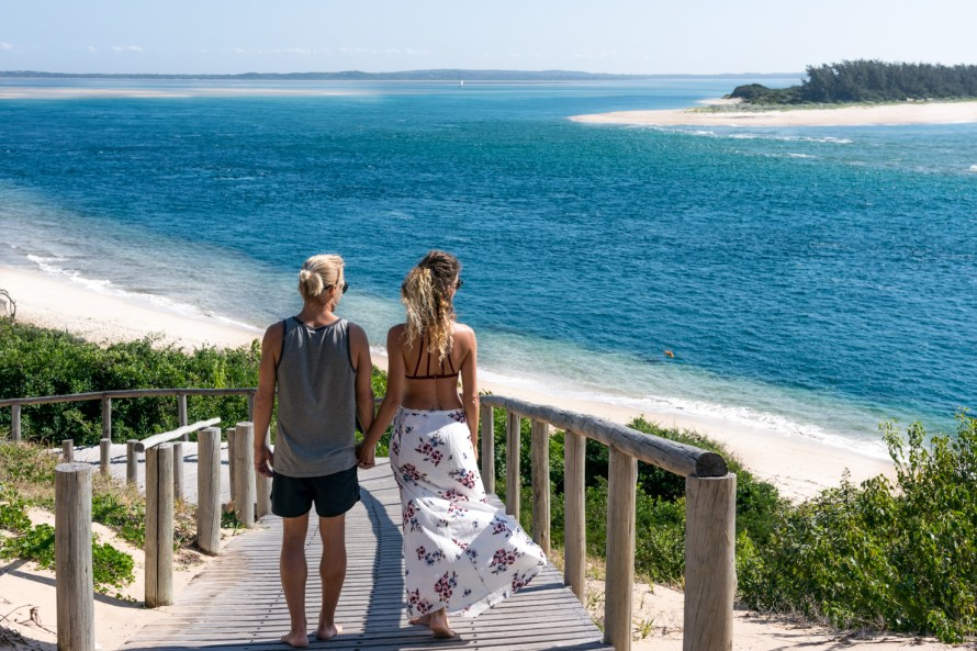 travel couple holding hands at machangulo beach lodge