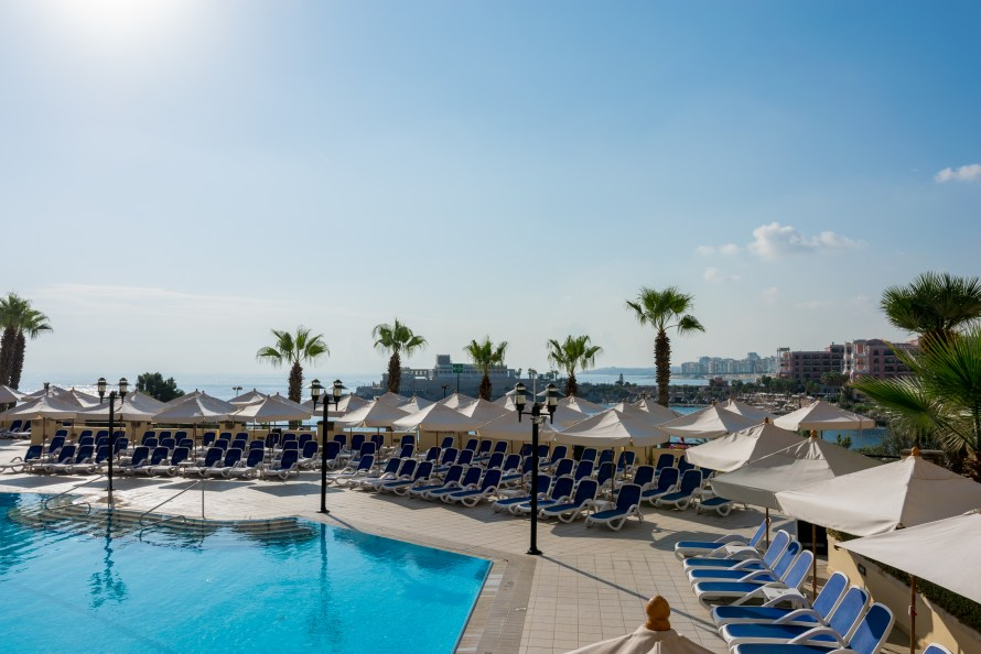 pool chairs and umbrellas at Corinthia Hotel St. George's Bay Malta