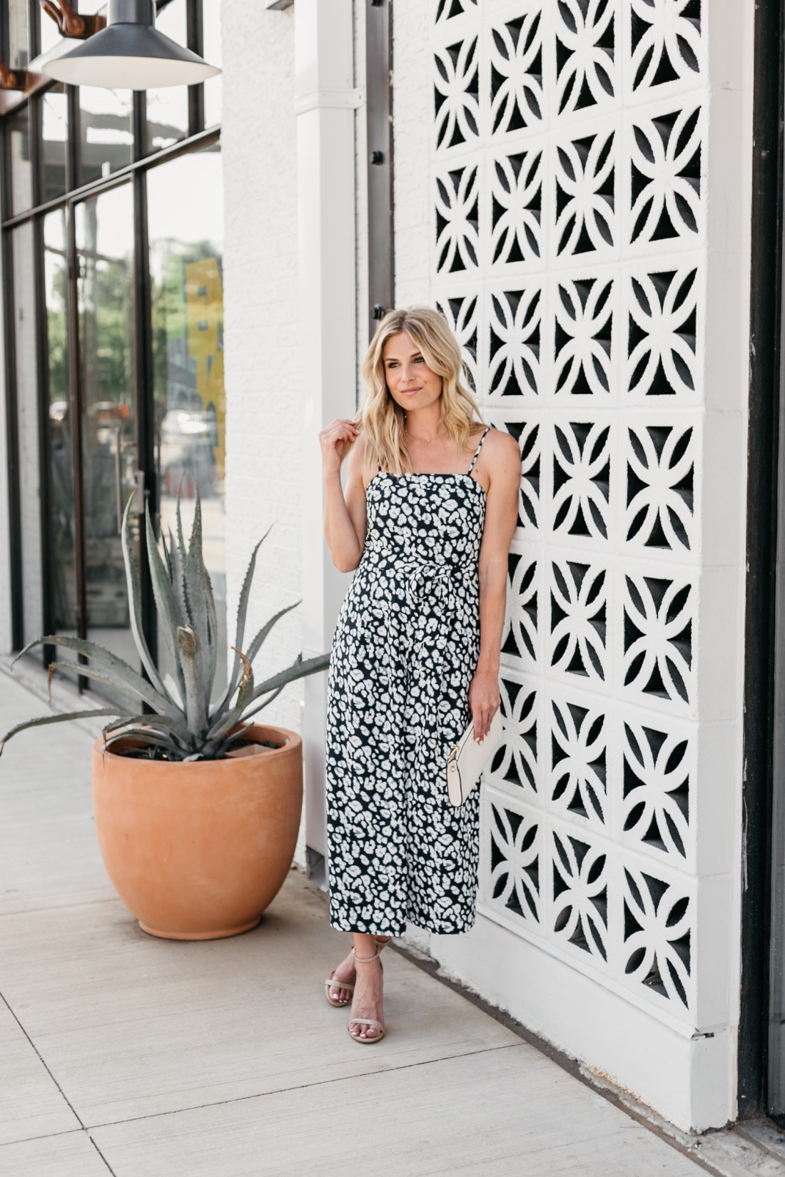 summer vacation outfits - One Small Blonde is wearing a navy leopard jumpsuit from Banana Republic