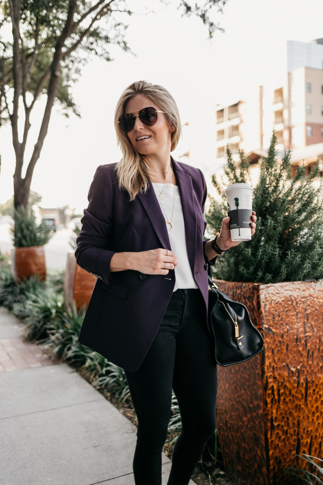 wear plum to work with this look of a girl wearing shades with a coffee cup in her hand