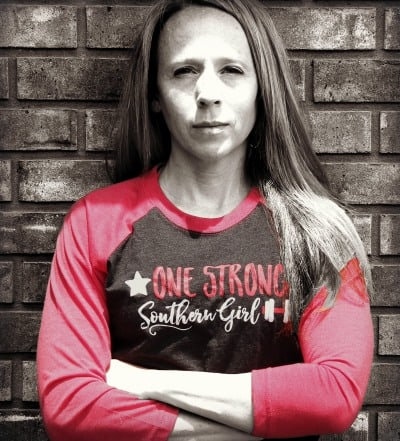 an image of One Strong Southern Girl with red and black logo shirt against brick wall