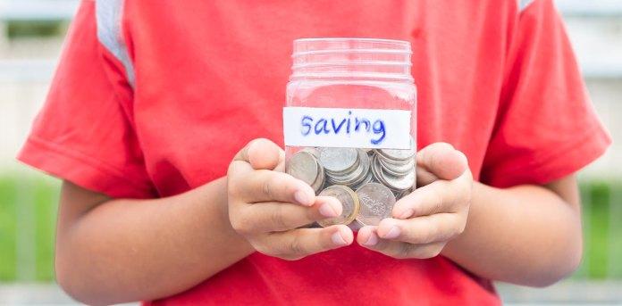 kid saving money in a jar