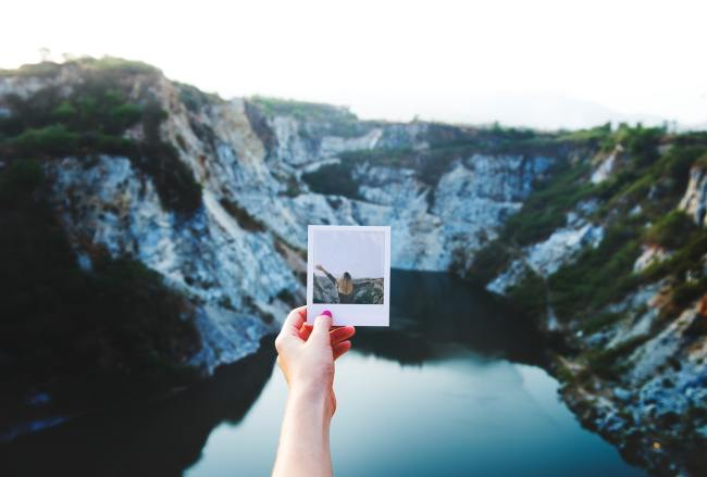 holding a photo above a canyon