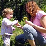 baby and mother with dandelions