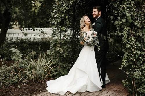 bride wearing custom altered wedding gown and groom wearing custom made tuxedo