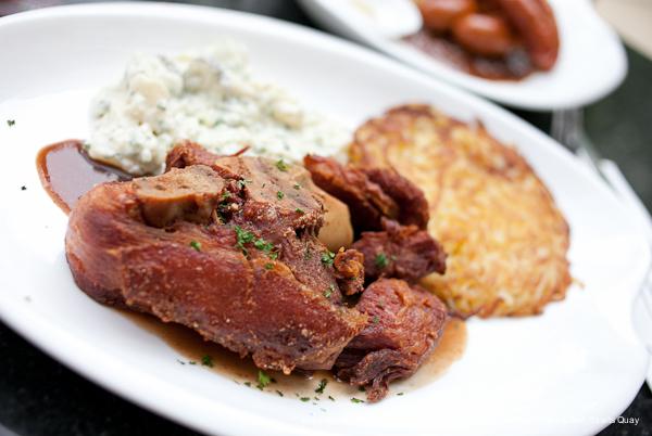 Crispy German Pork Knuckle with gravy served with German Potato Salad and Rösti