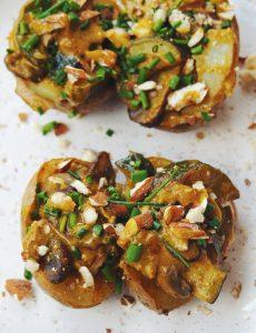 Pommes de terre farcies aux champignons et courgettes, sauce lait de coco et curry (vegan, sans gluten). Parsemées d'amandes concassées et de ciboulette.