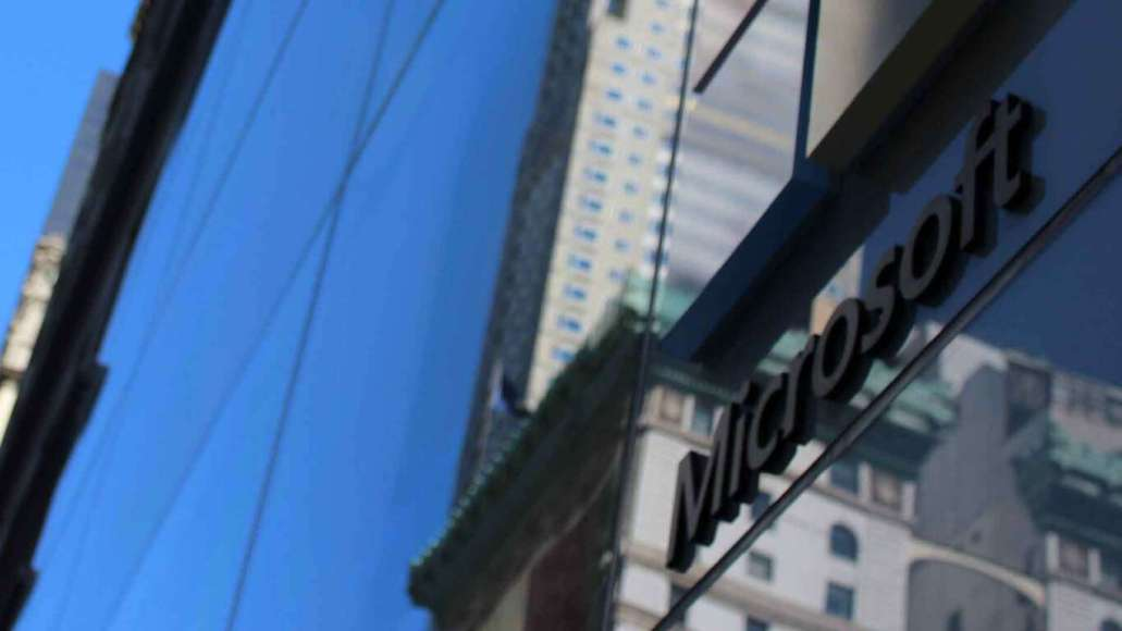 A Microsoft logo on a glass wall witha reflection of a blue sky