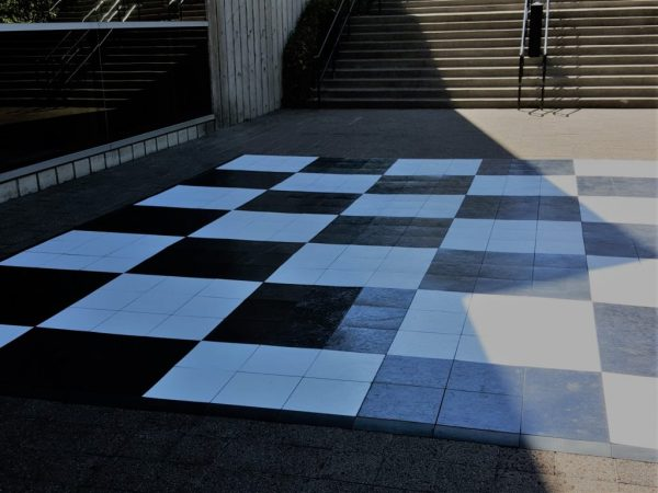 Black and white large checkered dance floor laid outside
