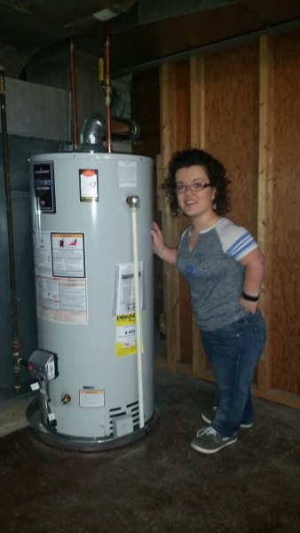 Athina Morehouse standing next to the water heater.