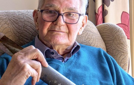 David Pearce holding an old disabled, incendiary bomb