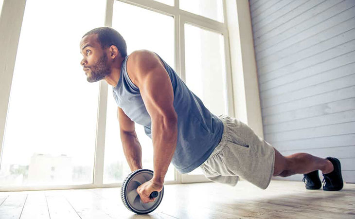 Man Using Ab Wheel Rollout Exercise For Fitness