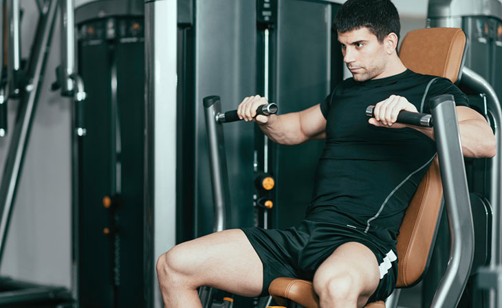 Man Working Out Seated Machine Chest Press