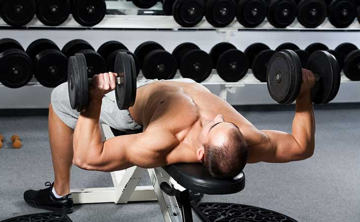 Man Working Out Chest By Pressing Dumbbells Exercise