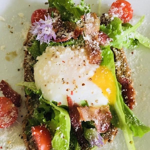 Gepocheerd ei op toast met sla, spekjes, tomaat & parmezaan