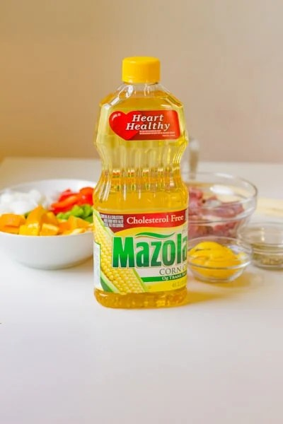 a bottle of mazola corn oil on a table with pork tenderloin ingredients