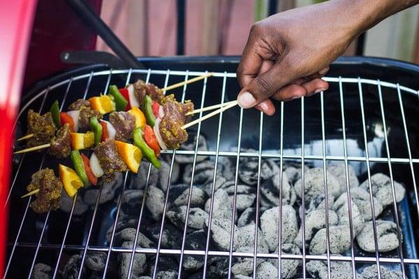 pork tenderloin kabobs being placed on a grill