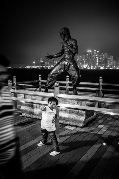 A boy poses in front of Bruce Lee's statue, Avenue of Stars, Hong-Kong