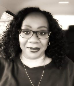 Black woman wearing glasses with curling hair to shoulders