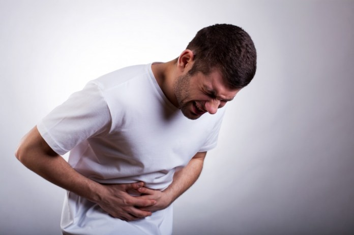 Young man with severe stomachache holding his stomach