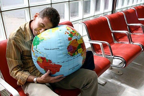 Precision-Nutrition-Blog-All-About-Jet-Lag-Airport-Sleeping-On-Globe-Ball