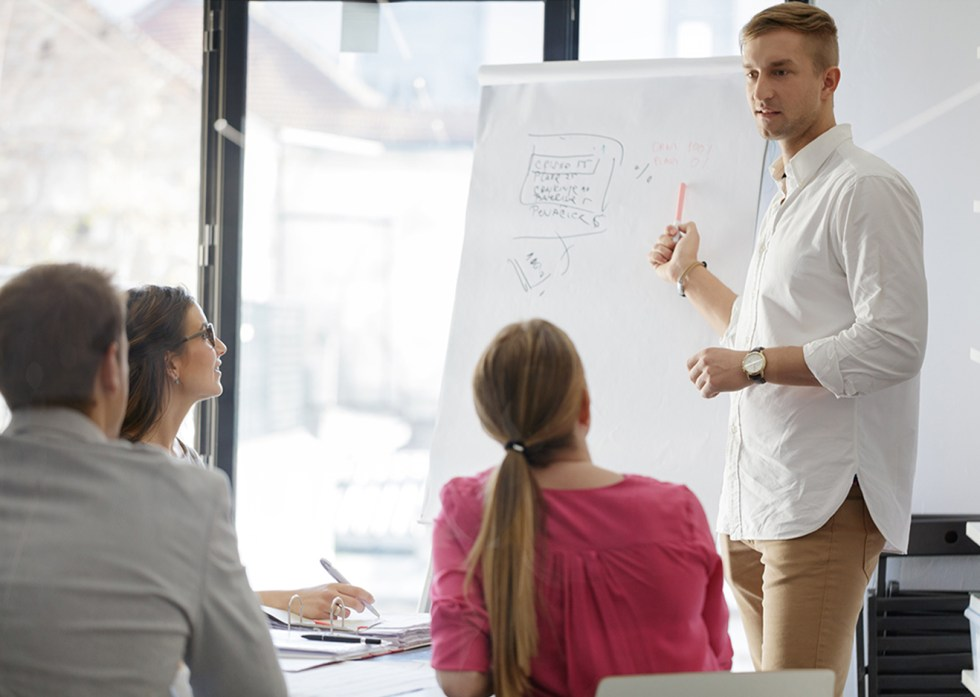Group of business people on a meeting, businessman standing in front of flip chart
