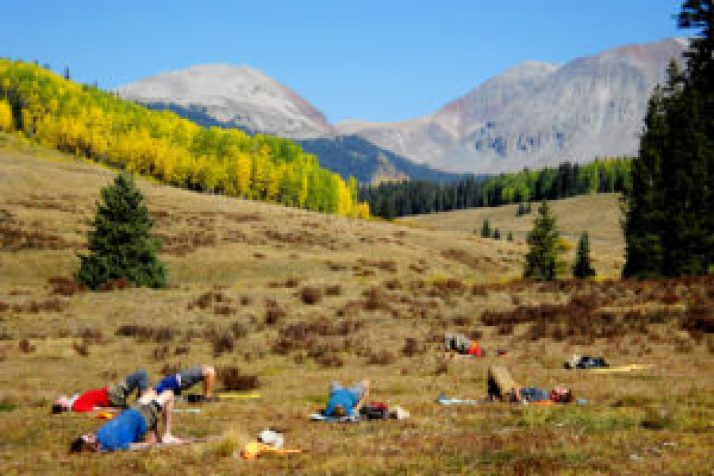 A group of students at Open Sky Wilderness Therapy enjoying the outdoors while stretching.