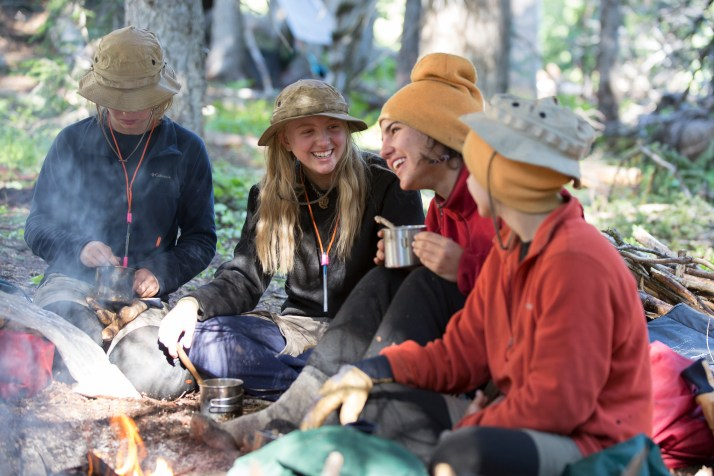 A group of Open Sky Wilderness Therapy students laughing around a campfire.
