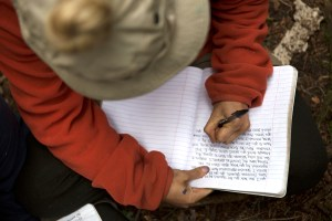 An Open Sky Wilderness Therapy student journaling their thoughts at a campsite.