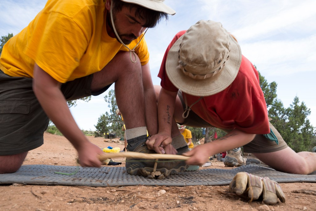 Two Open Sky Wilderness Therapy students work together to bow drill a fire.