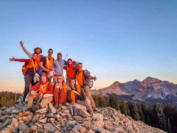 Open Sky Wilderness Therapy field guides pose for a photo on top of a mountain during orientation.