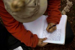 Adolescent Girl student writes letter to family at Open Sky Wilderness Therapy