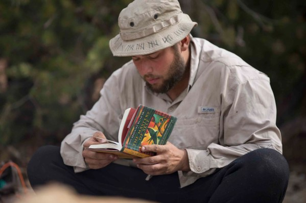 A student reads a book during his solo experience in wilderness.