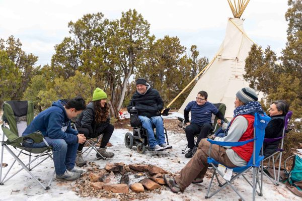 Family at new Open Sky Family Services base camp site with wheelchair accessible paths and tipi.