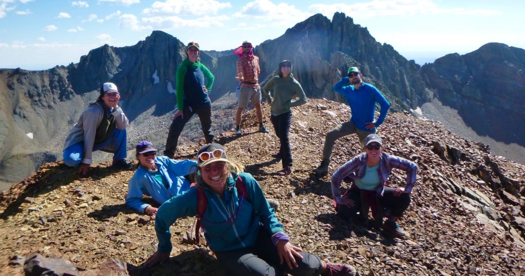 A group of Open Sky Wilderness therapy guides smile together on top of a mountain.