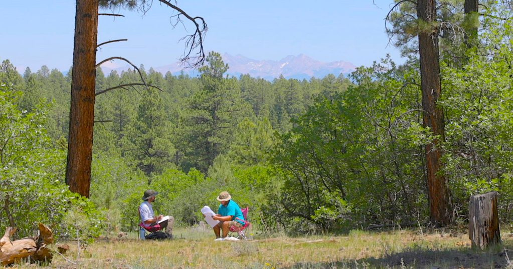 Open Sky Wilderness Therapy clinical therapist Nick Basalyga sits with a student in a field with mountains in the background.