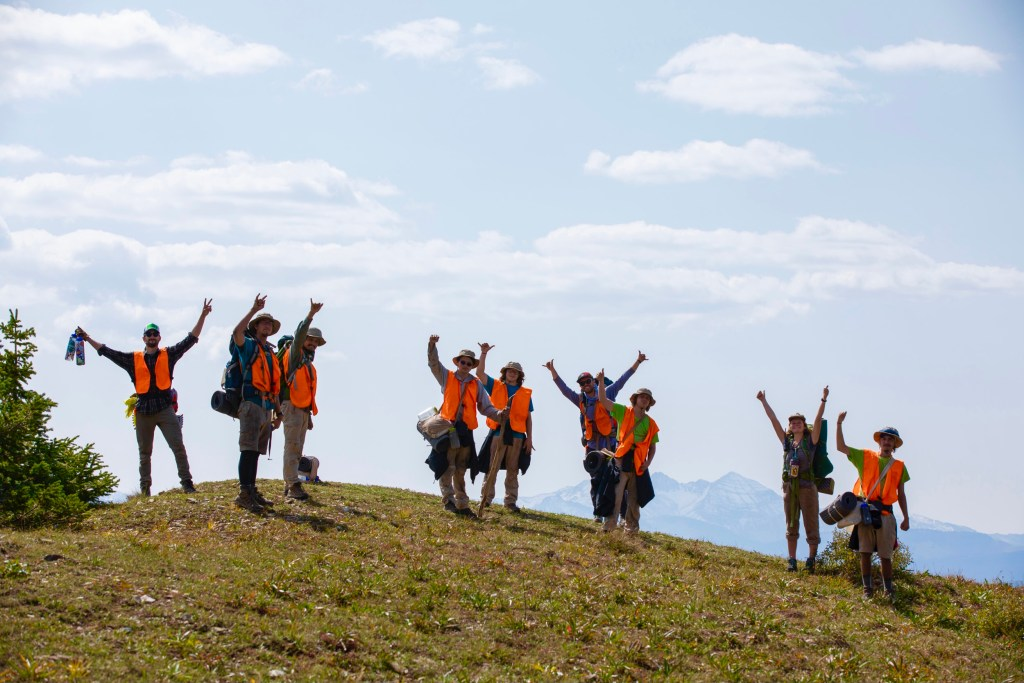 A group of young adult students at Open Sky Wilderness Therapy raise their arms above their heads as they reaach the summit of a mountain.